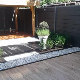 Achtertuin met composiet schutting, keramische tegels en veranda van douglas hout